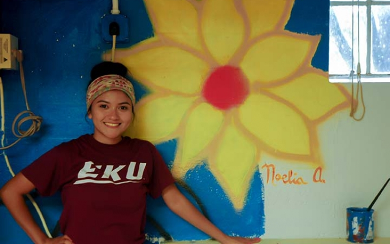 Art student standing in front of painting of a large yellow flower.